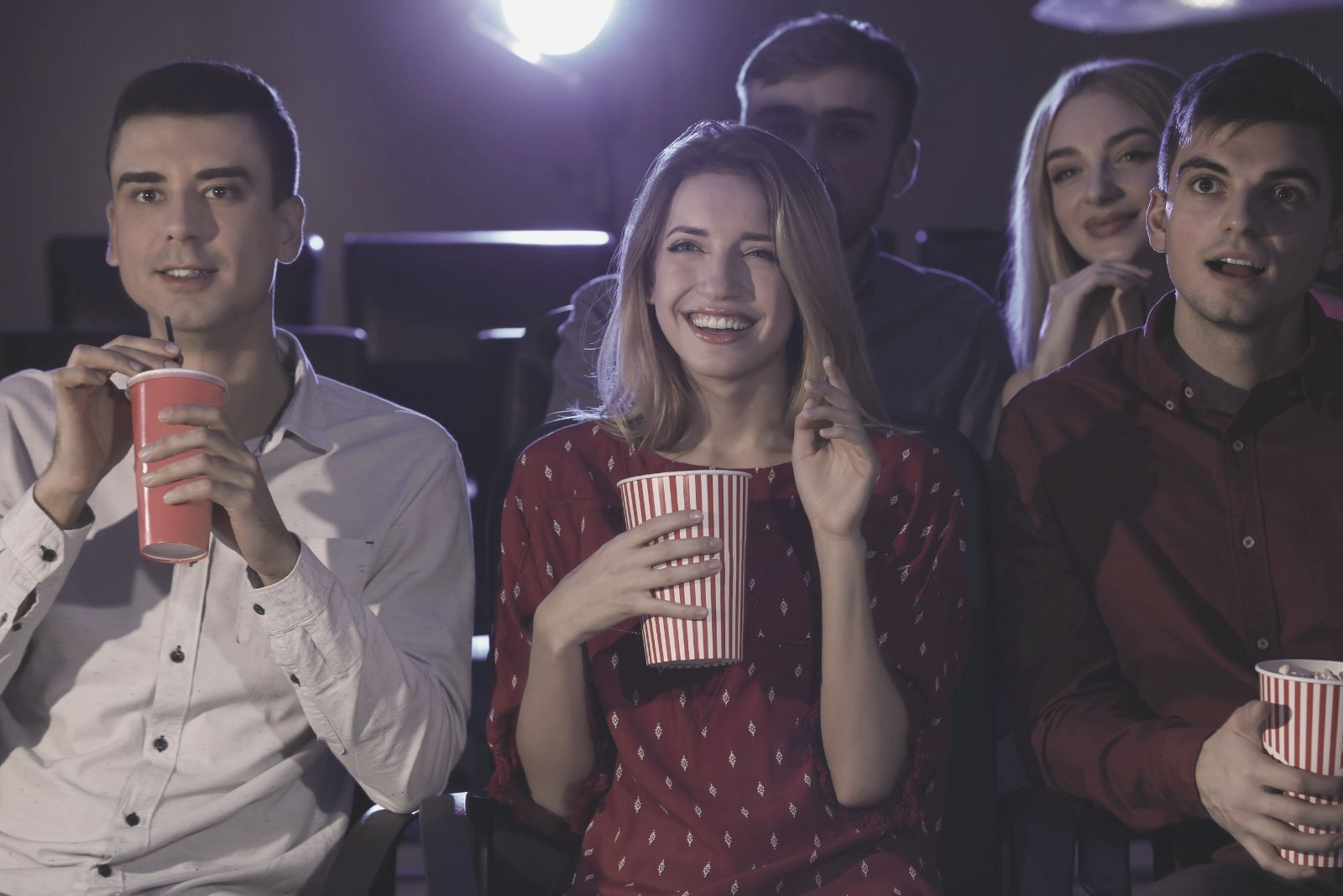 men and women watching movie in the cinema laughing and eating food