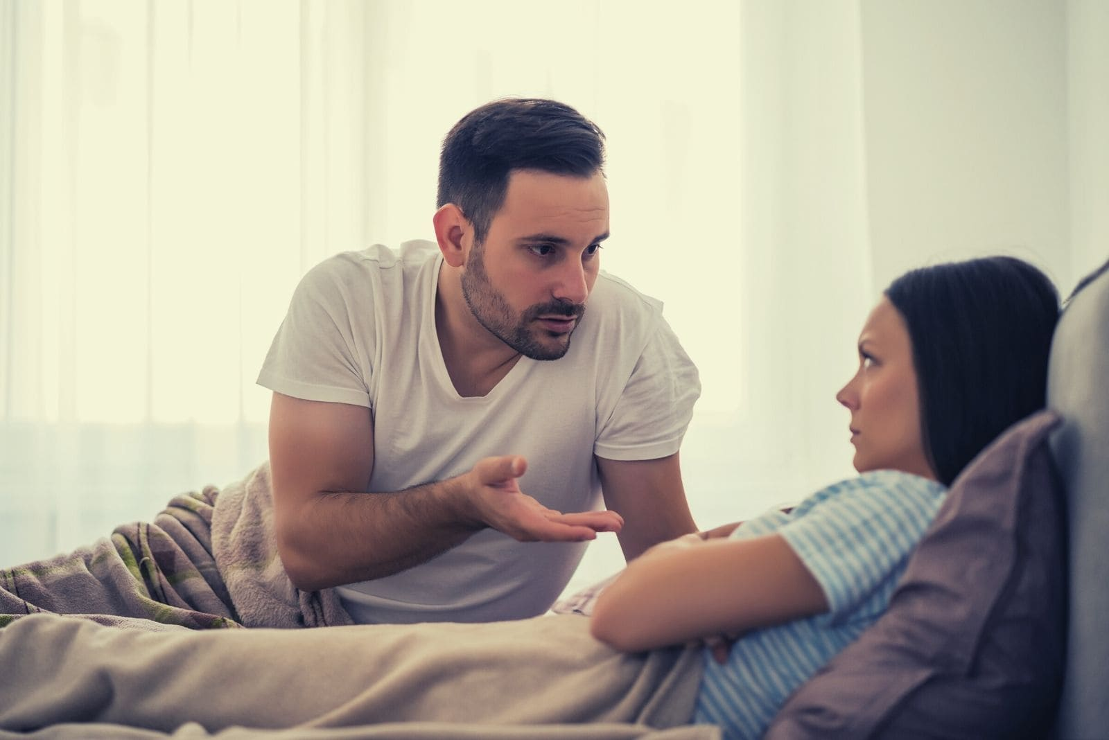 offended angry woman lying in bed beside a man explaining inside the bedroom
