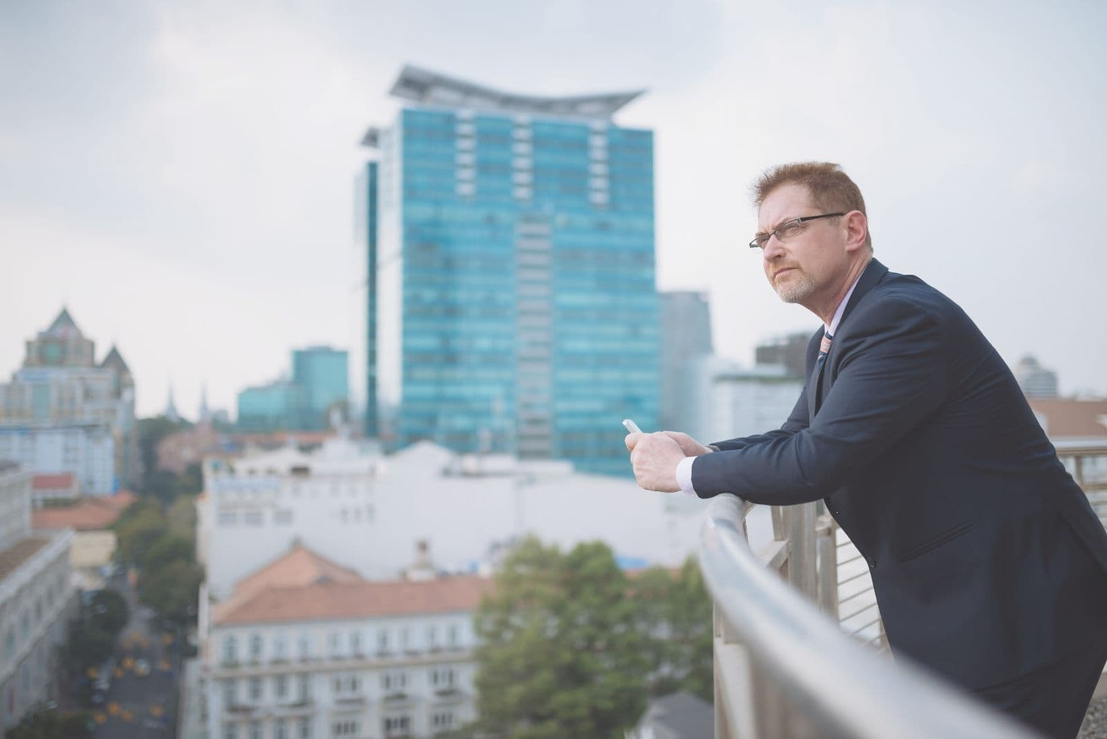 pensive business man standing on the porch of the building holding a phone