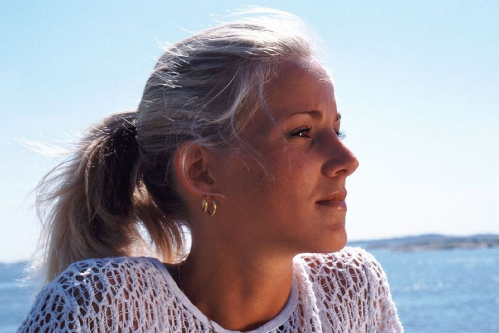 pensive caucasian woman in a close up photography near the body of water