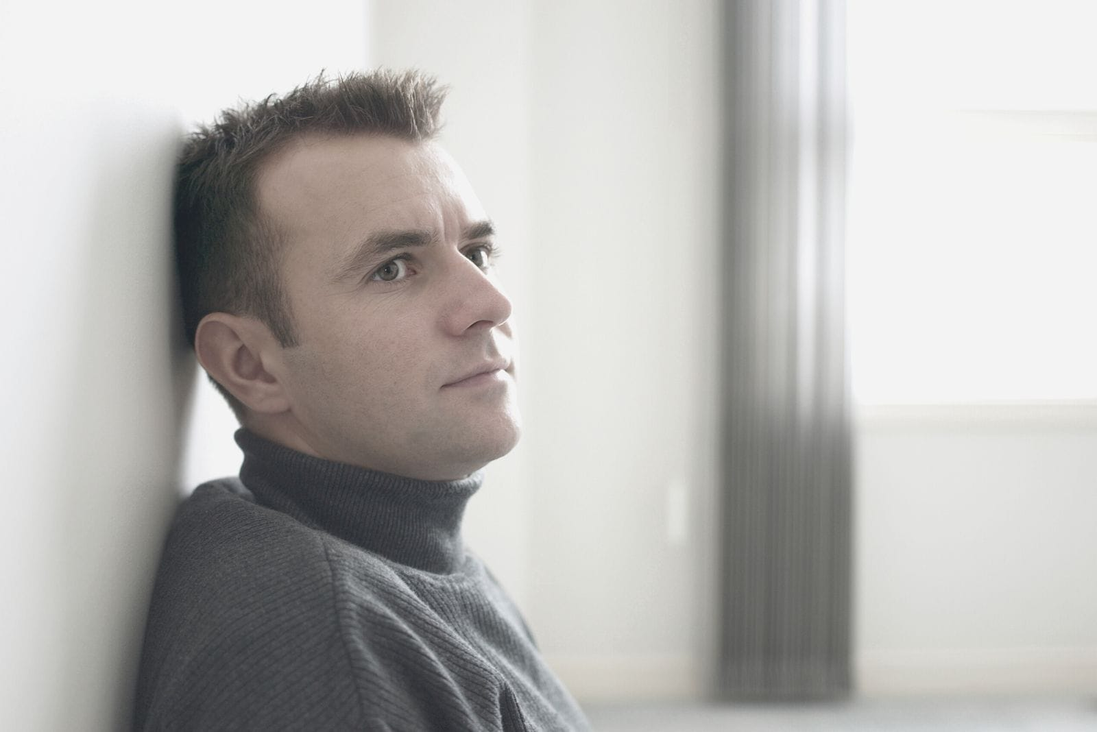 pensive man leaning on the white wall inside the house in close image
