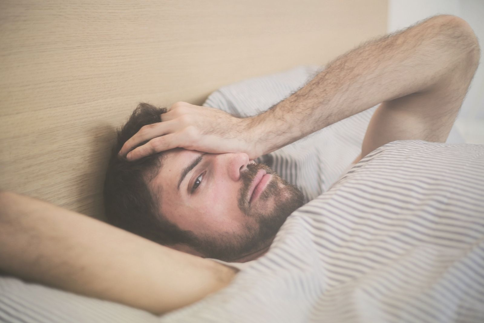 pensive man lying in bed and covering his one eye with one hand