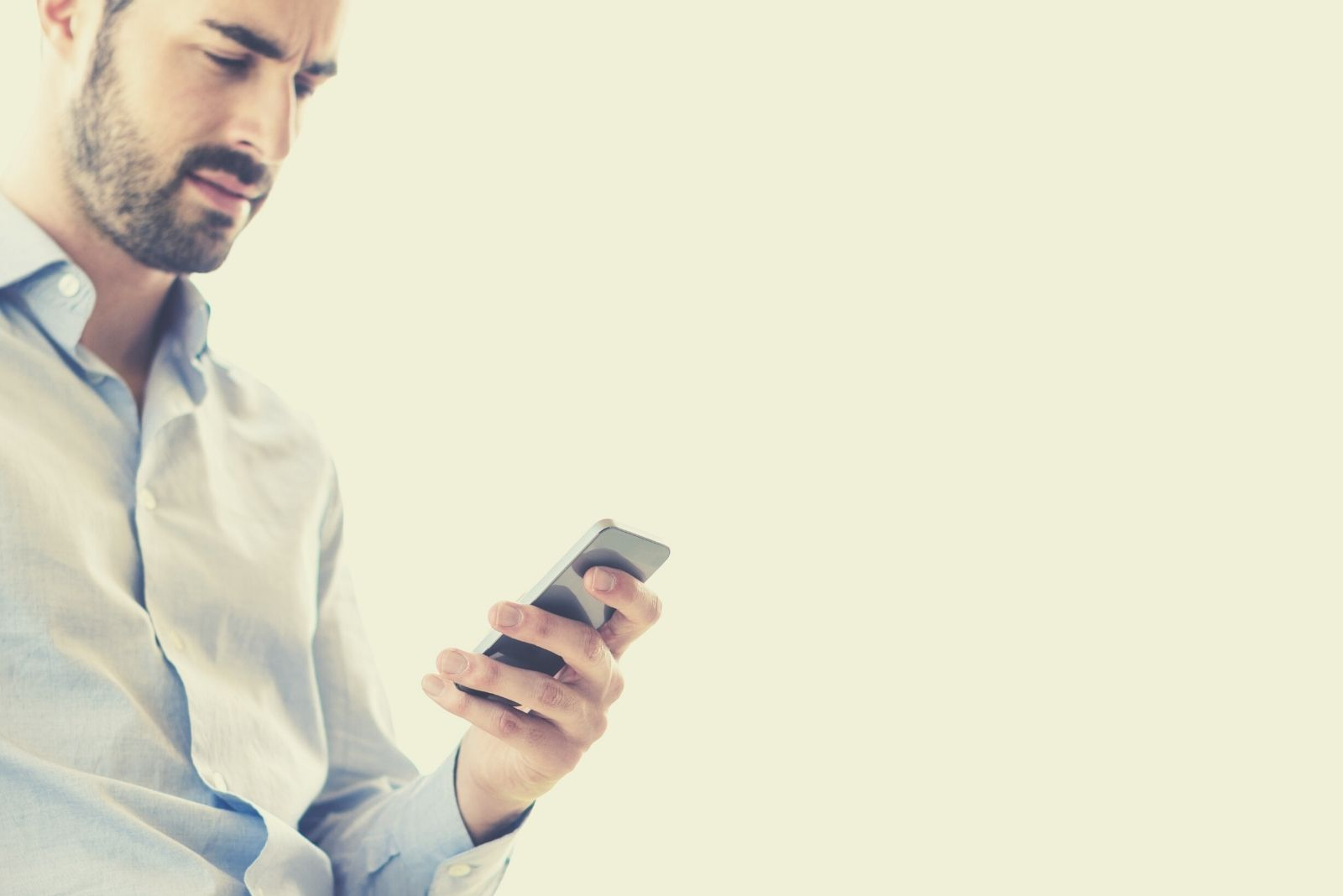 pensive man texting on his smartphone wearing smart casual with white background