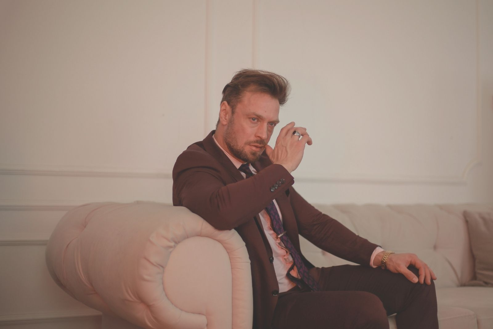 pensive man wearing a suit sitting on the sofa