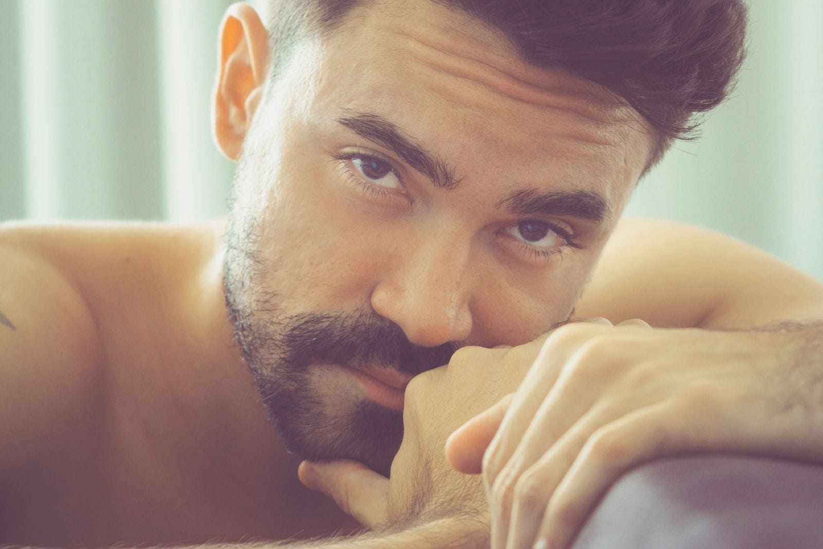 pensive man with beard in close up photography half naked looking at the camera