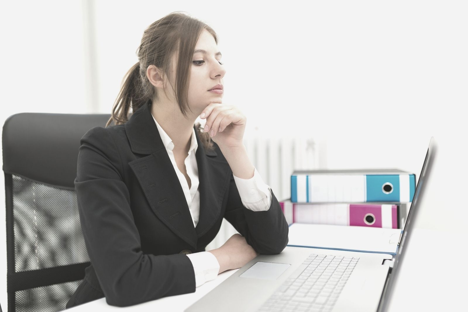 pensive office woman sitting by his table looking at the laptop and thinking deeply