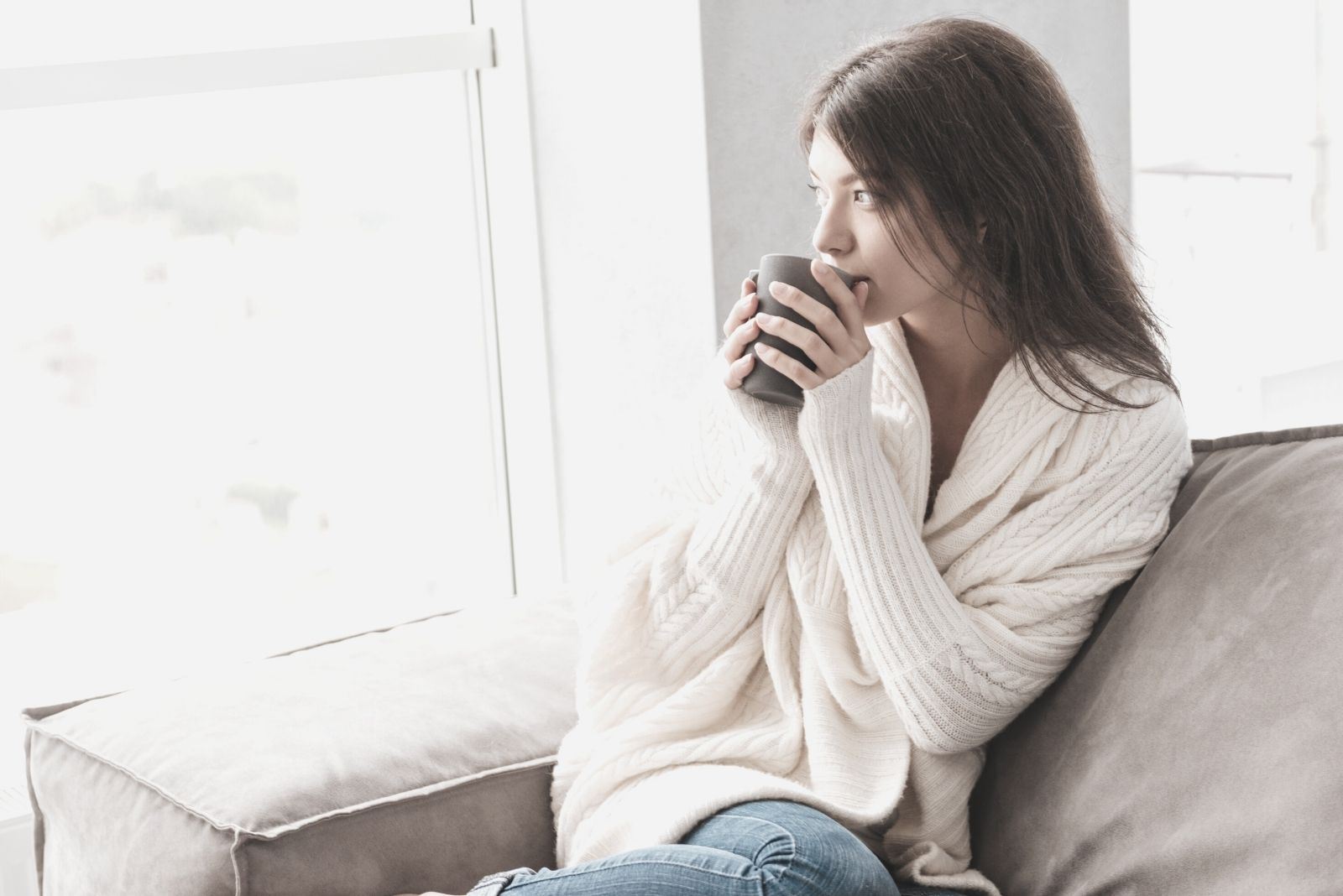 pensive pretty young woman sipping on her coffee early in the morning lounging in the couch near the windows