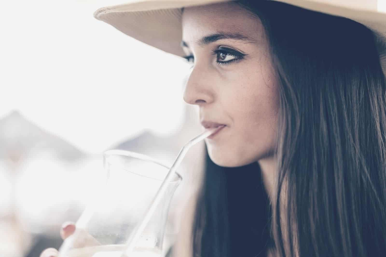 pensive woman drinking beverage in sideview close up photo wearing a hat