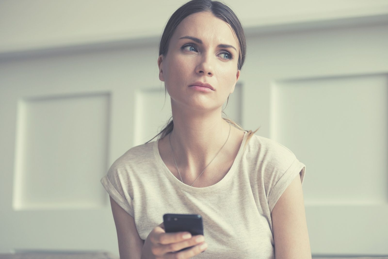 pensive woman on the phone looking away sad and sitting inside the house