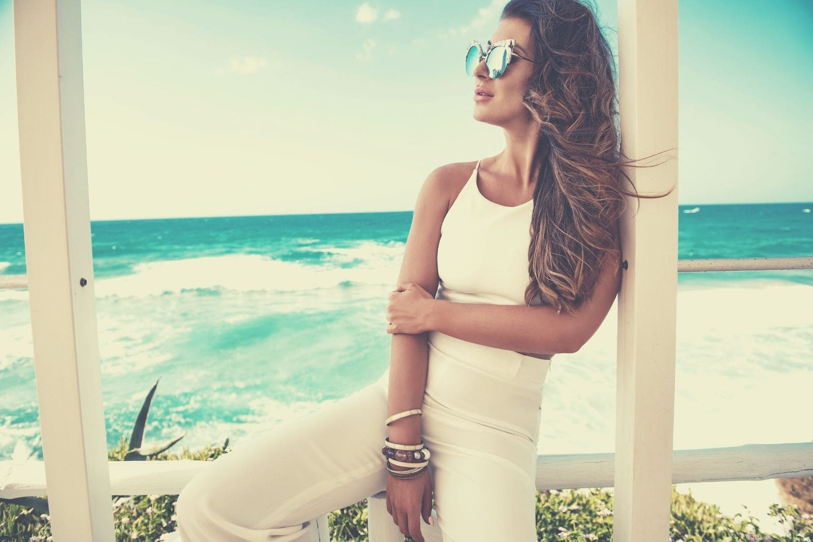 pensive woman on vacation sitting in the railings of a beach house wearing white fashionable dress and sunglasses