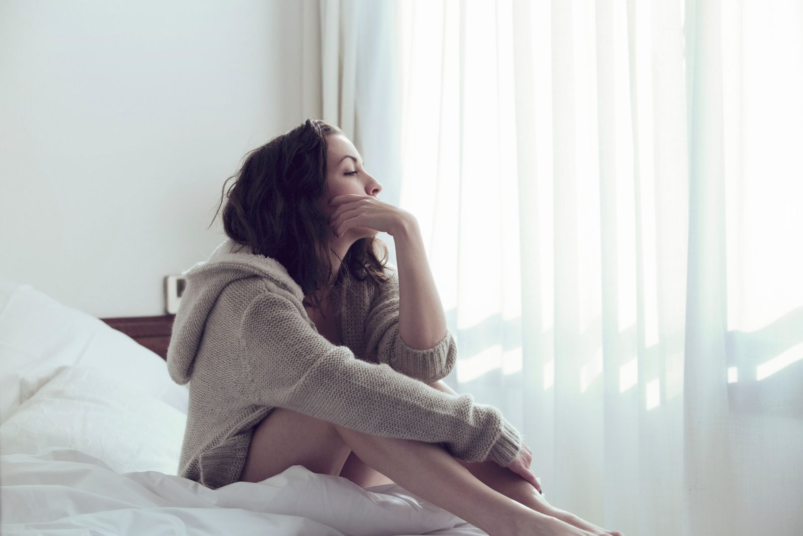 pensive woman sits on the bed wearing a big hoodie with hand on her face
