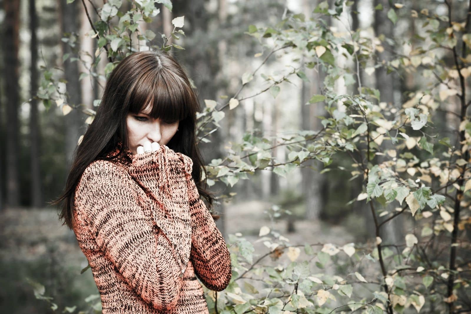pensive woman thoughtful wearing sweater standing in the middle of the forest
