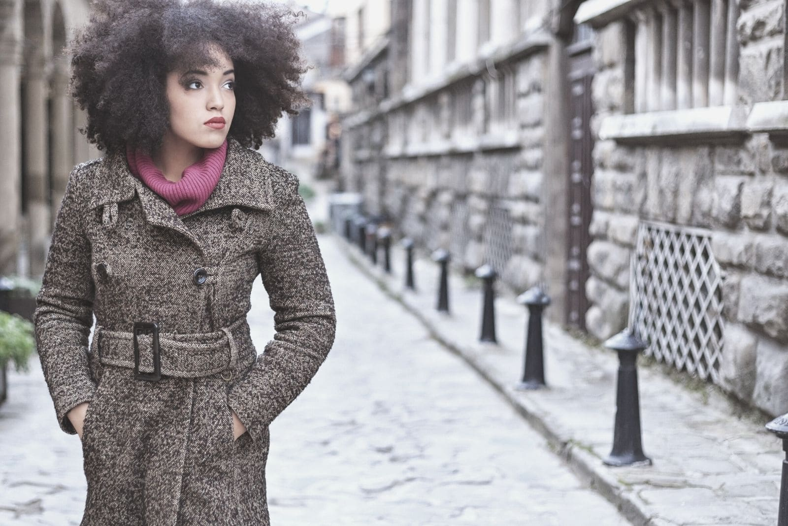 pensive woman walking on a narrow street with hands inside the pocket of her coat