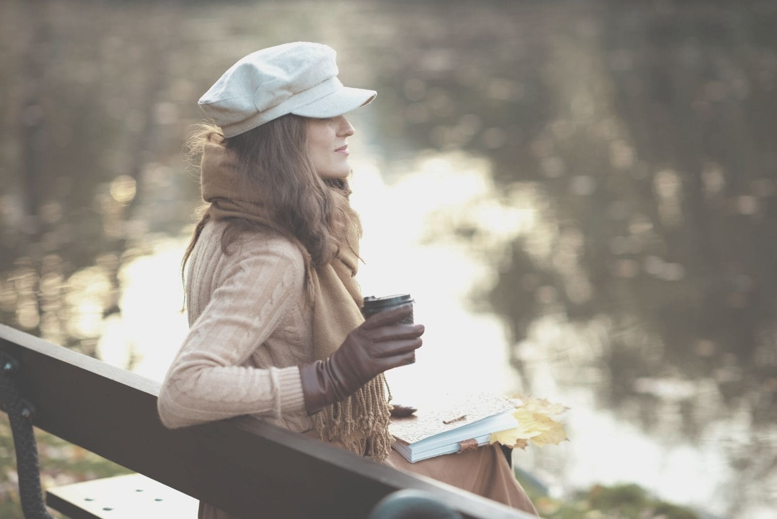 pensive woman with notebook and a cup of coffee and yellow leaves in the park