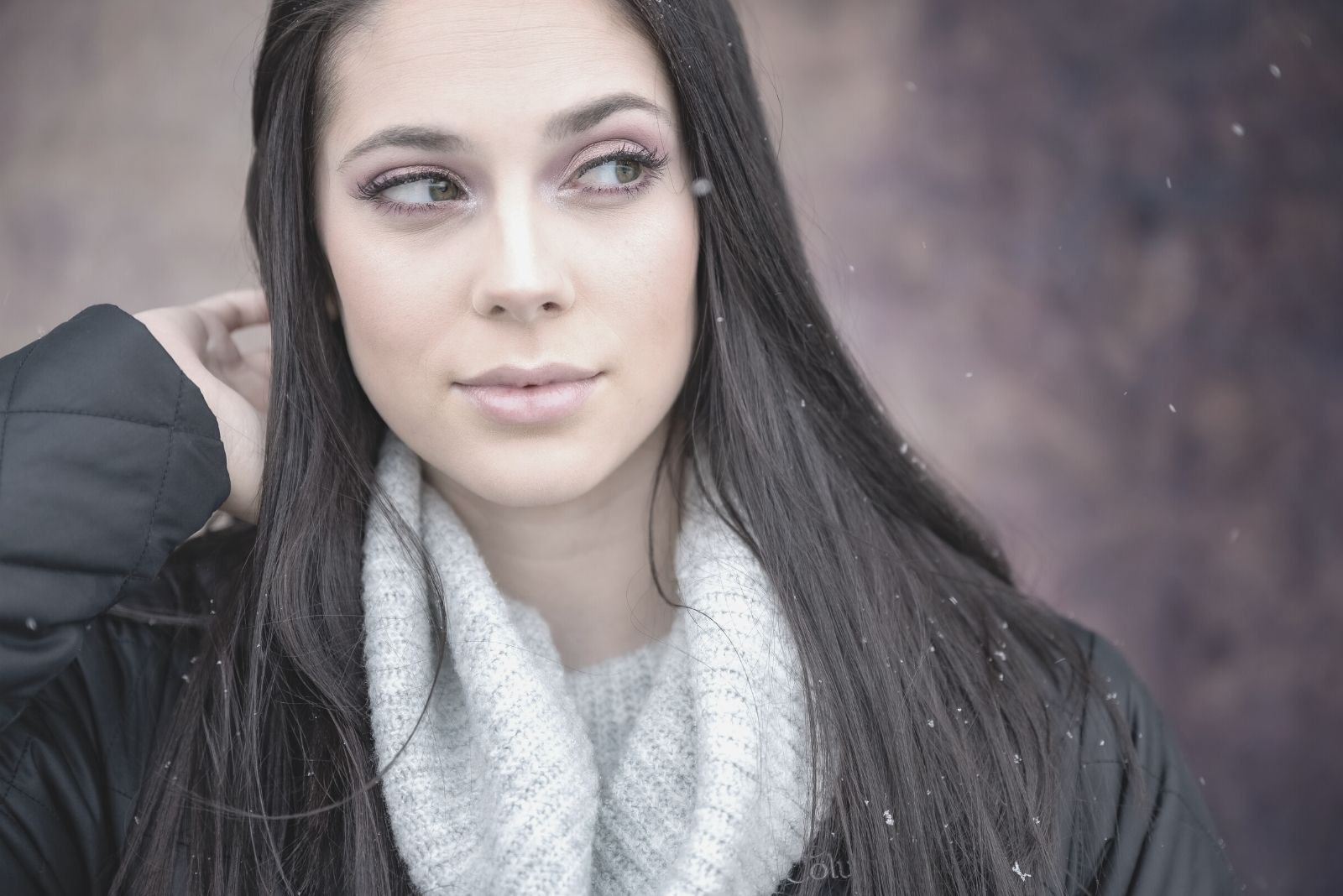 pensive woman with white scarf and black jacket looking at the side facing the camera