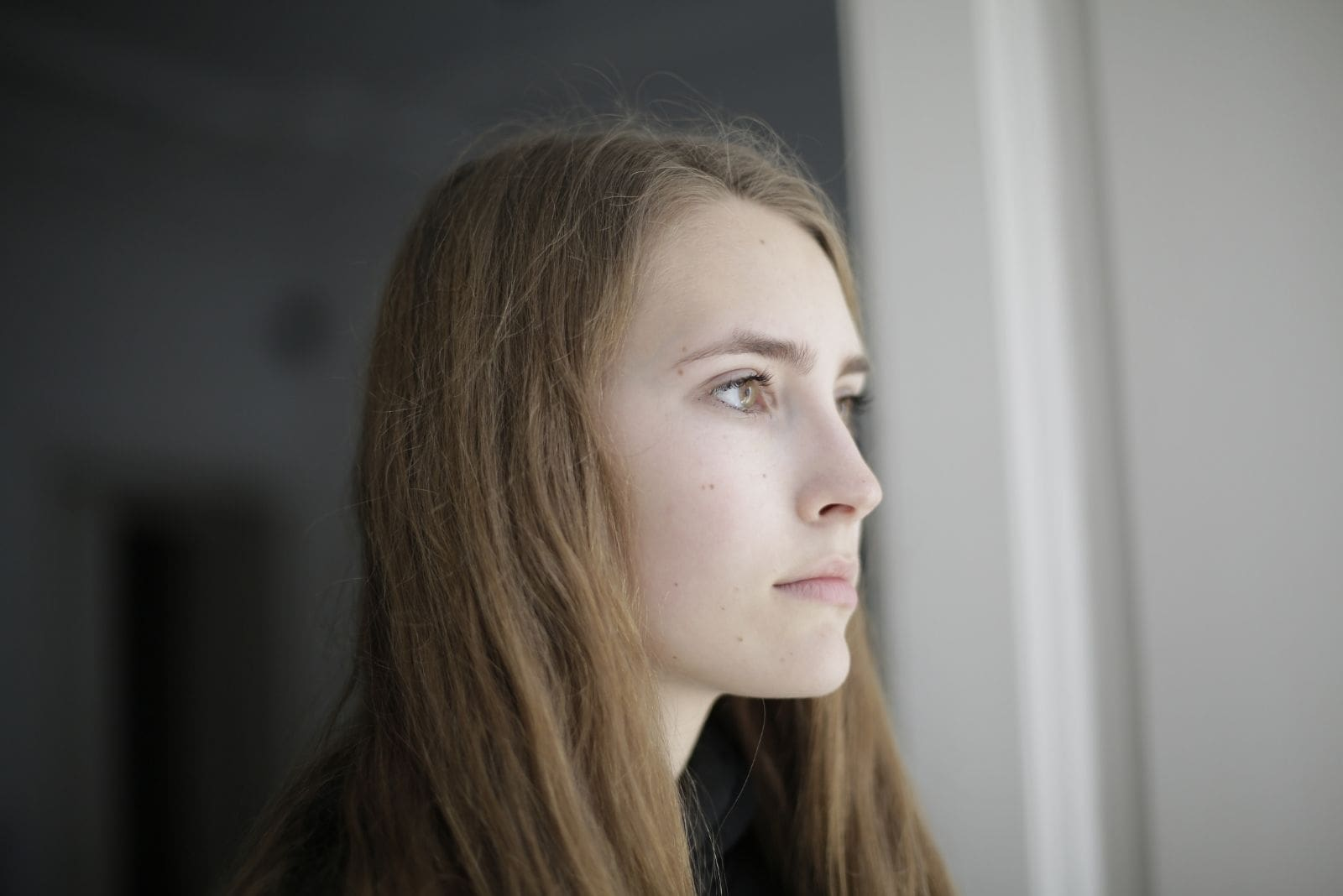 pensive young lady looking outside the window in close up photo