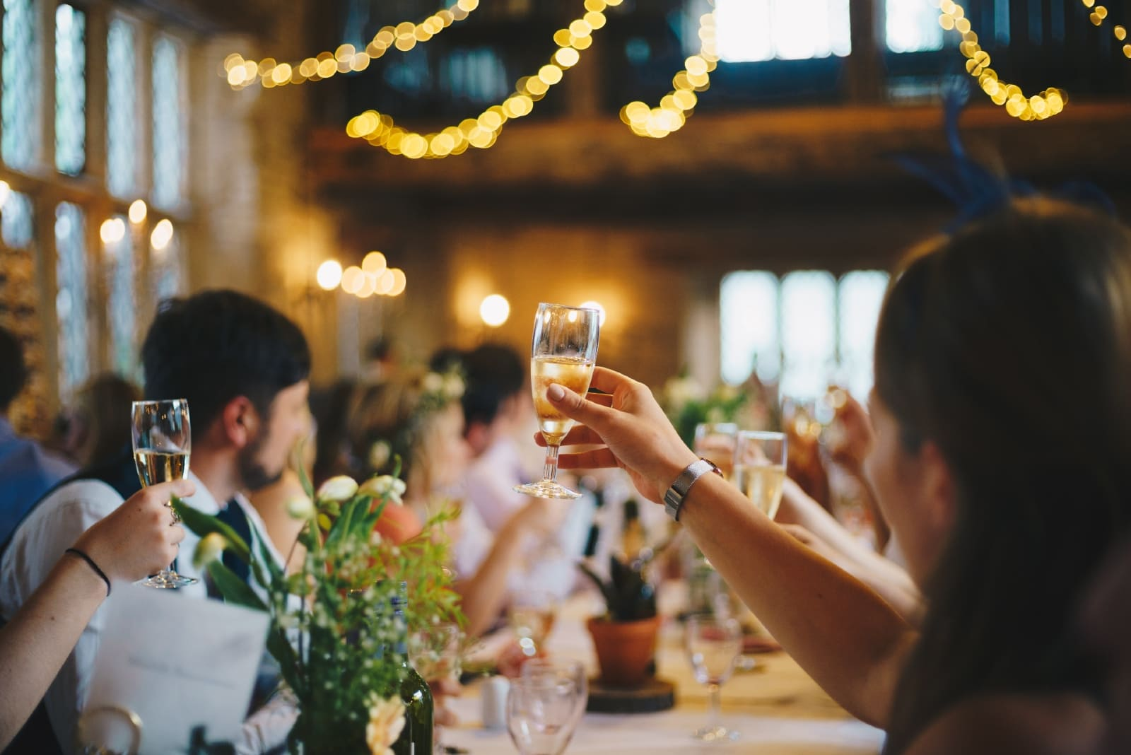 people raising wine glasses while sitting at table