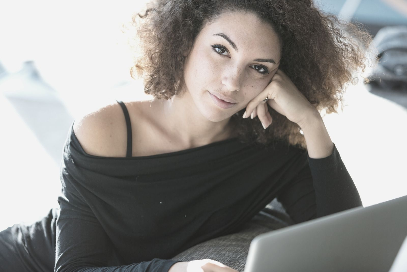 pretty curly haired woman lounging while working on laptop looking at the camera
