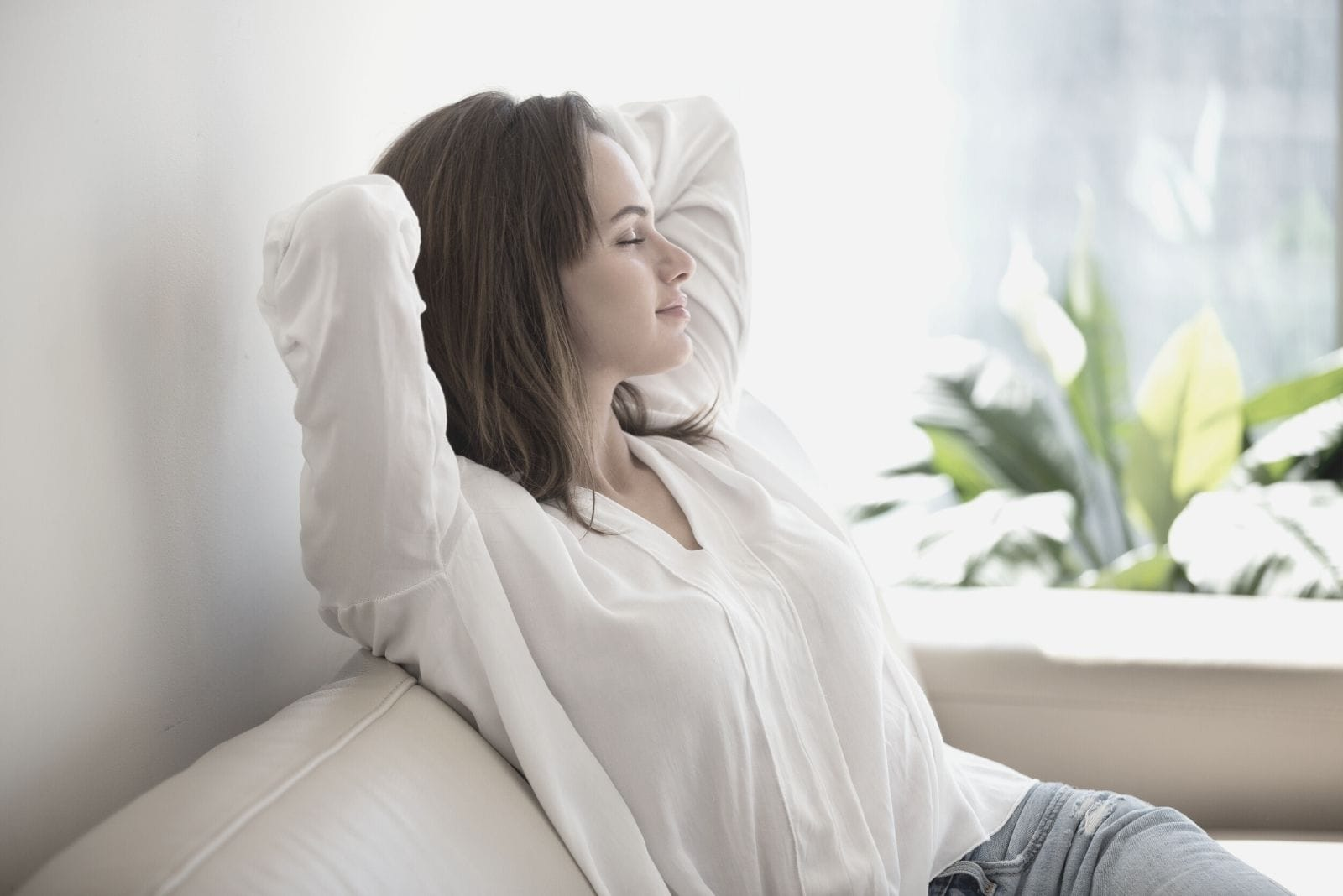 relaxed beautiful woman sitting comfortably in the sofa and closing her eyes