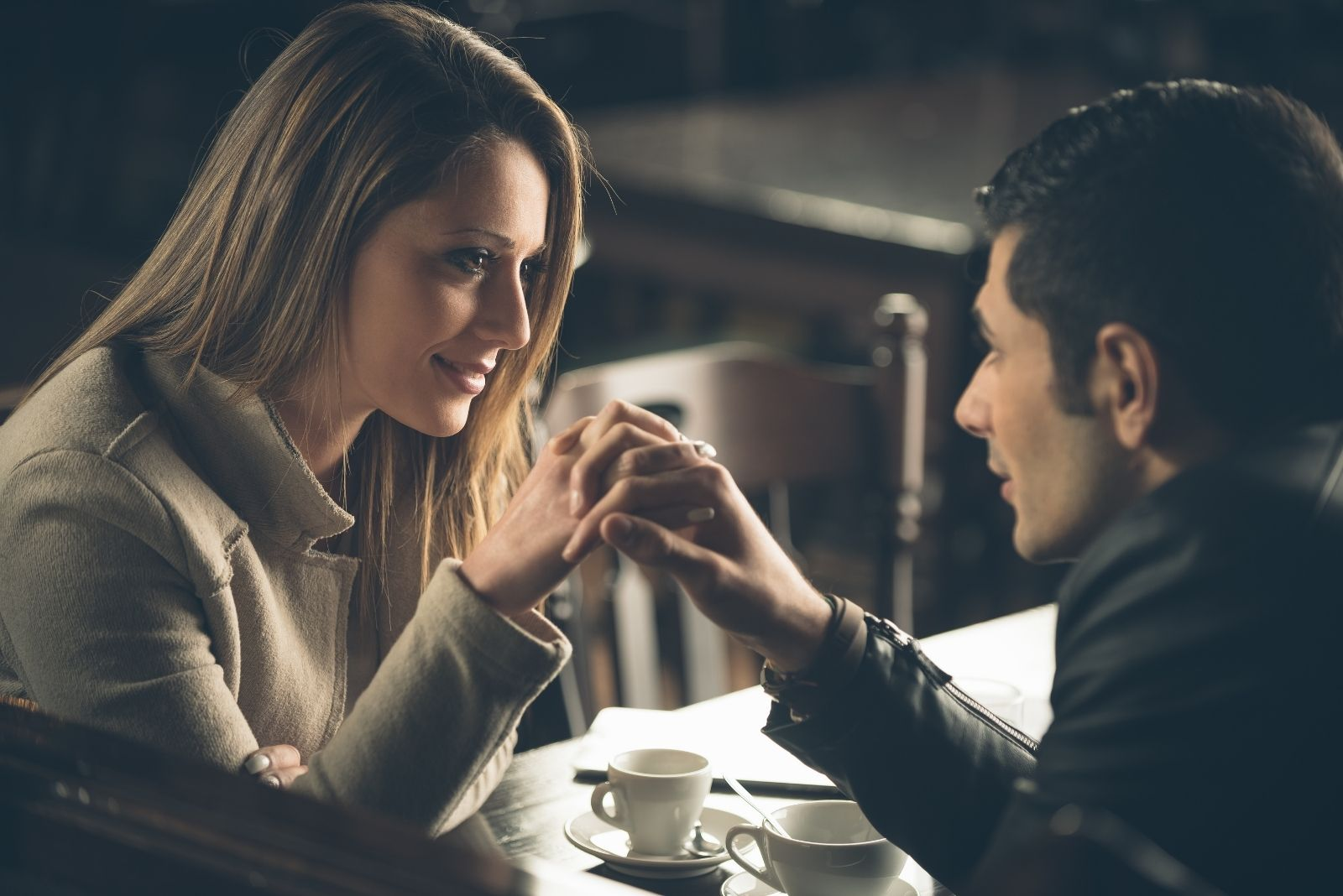 romantically clasping hands of the dating couple inside a cafe