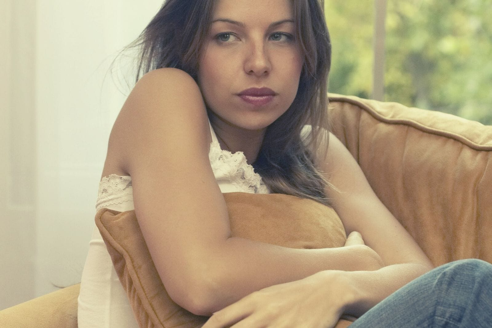 sad insecure woman embracing a pillow and sitting on the couch