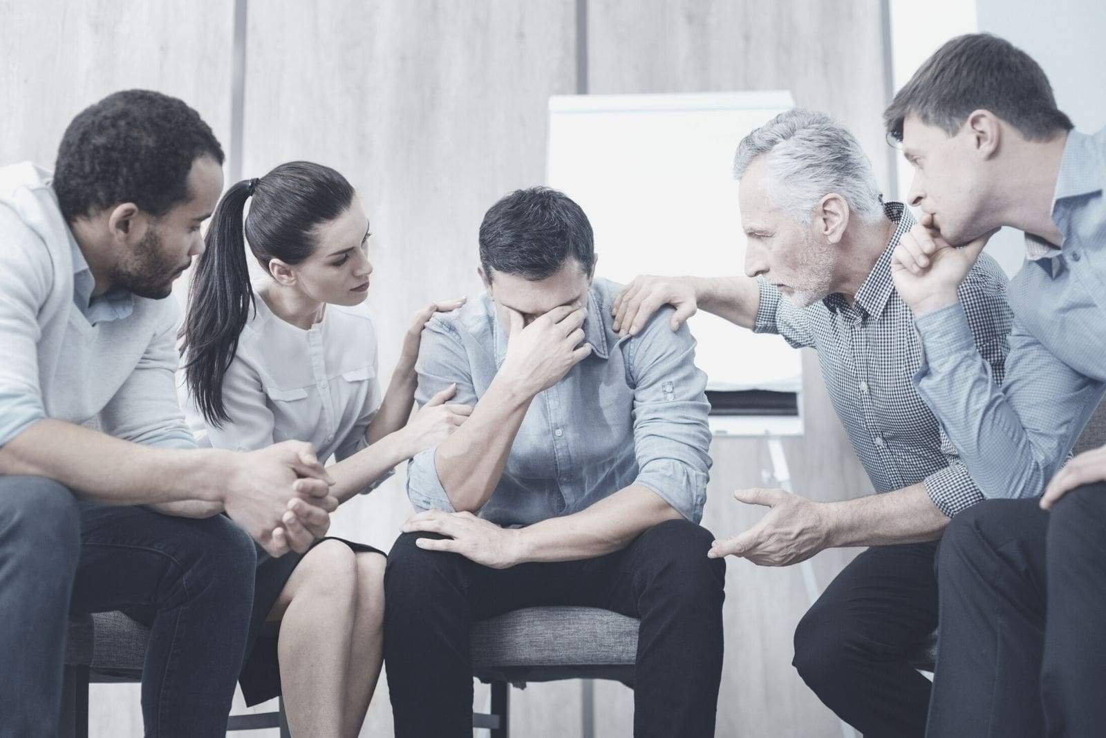 sad man crying in between colleagues listening to his story inside the office