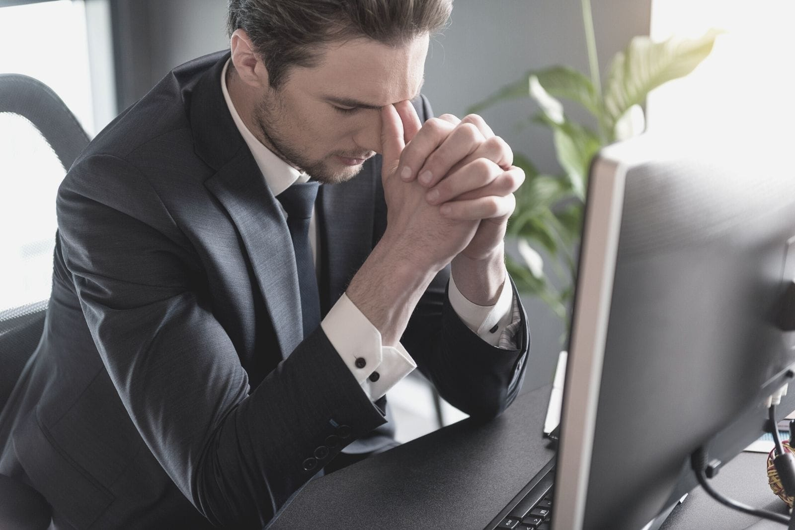 sad pensive man expressing frustration sitting by his office table in front of the computer