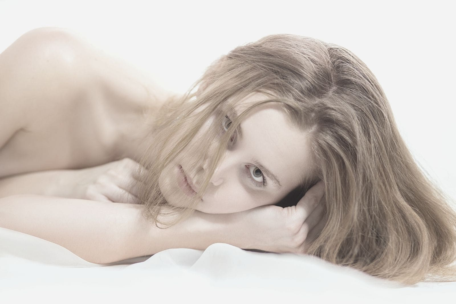 sad pensive pretty woman lying down on white linen bed looking at the camera naked in close up image