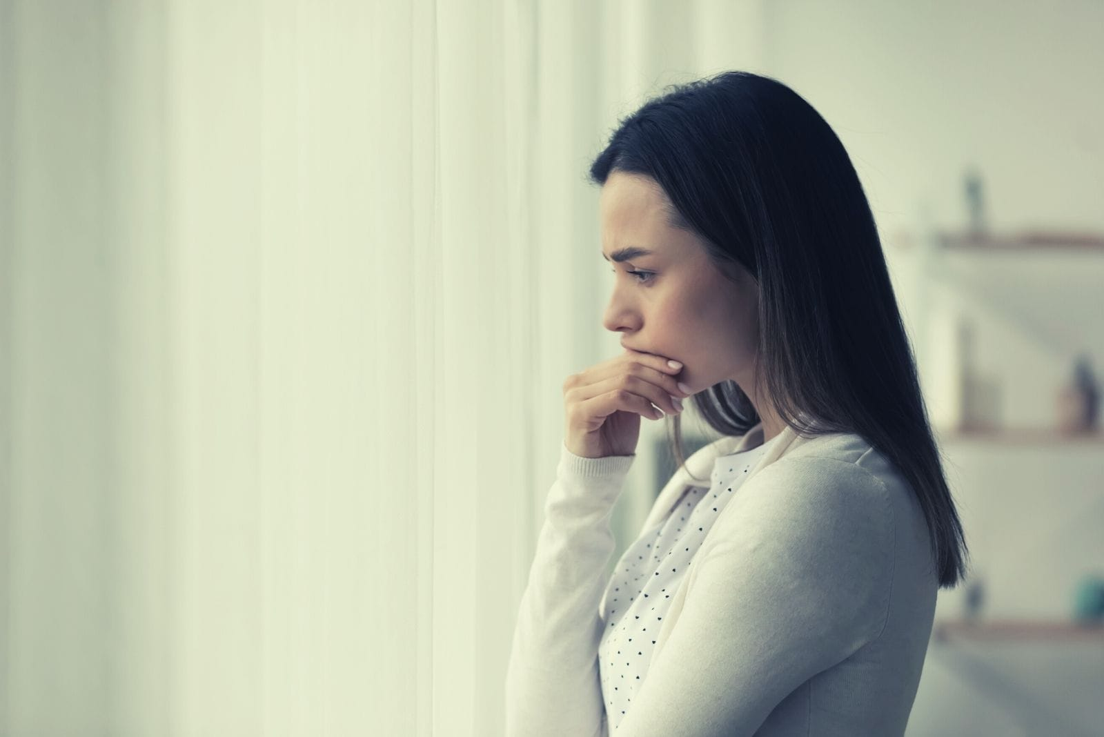 sad pensive woman standing near the windows looking for solution