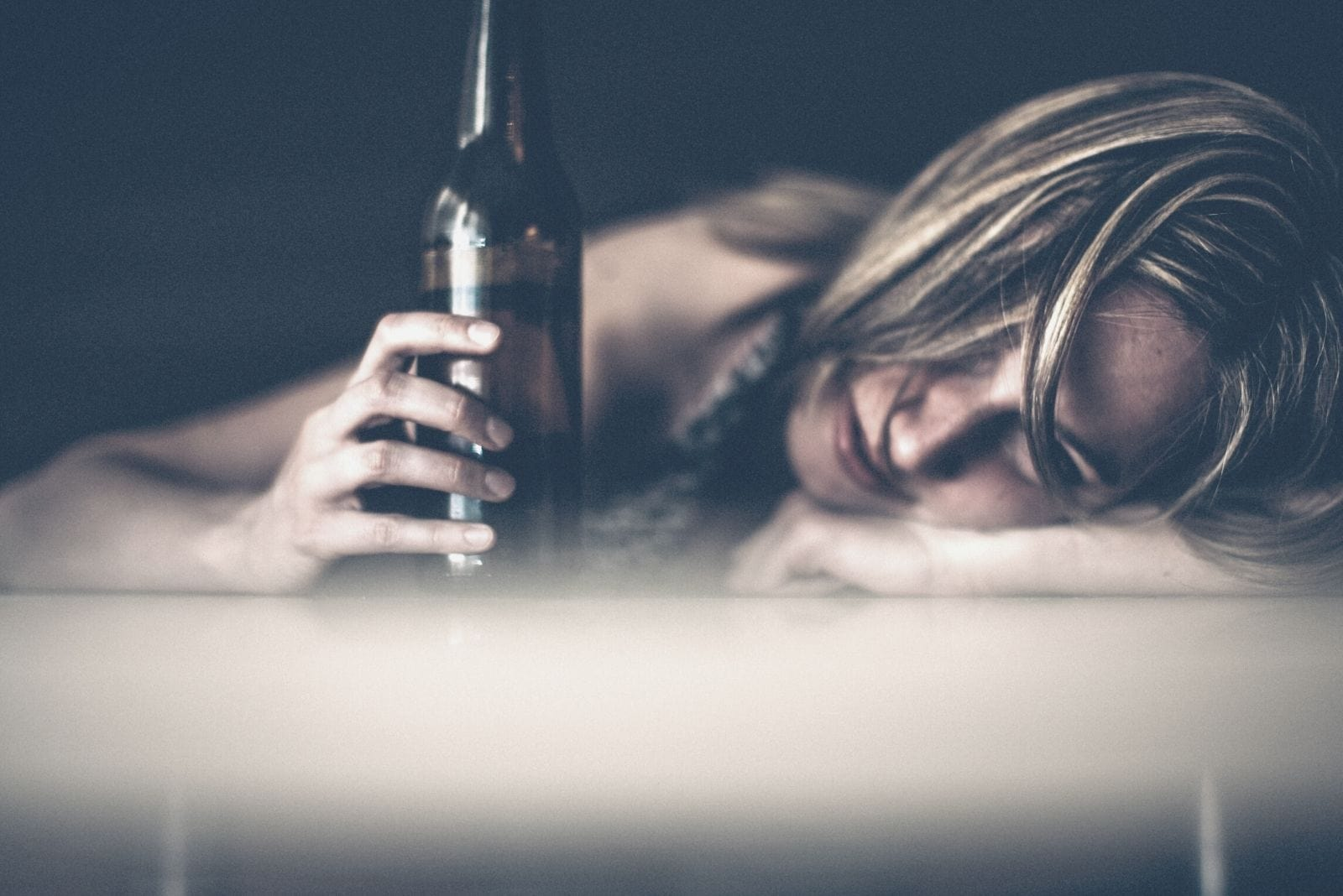 sad woman drinking and holding beer while crying and leaning her head on the table