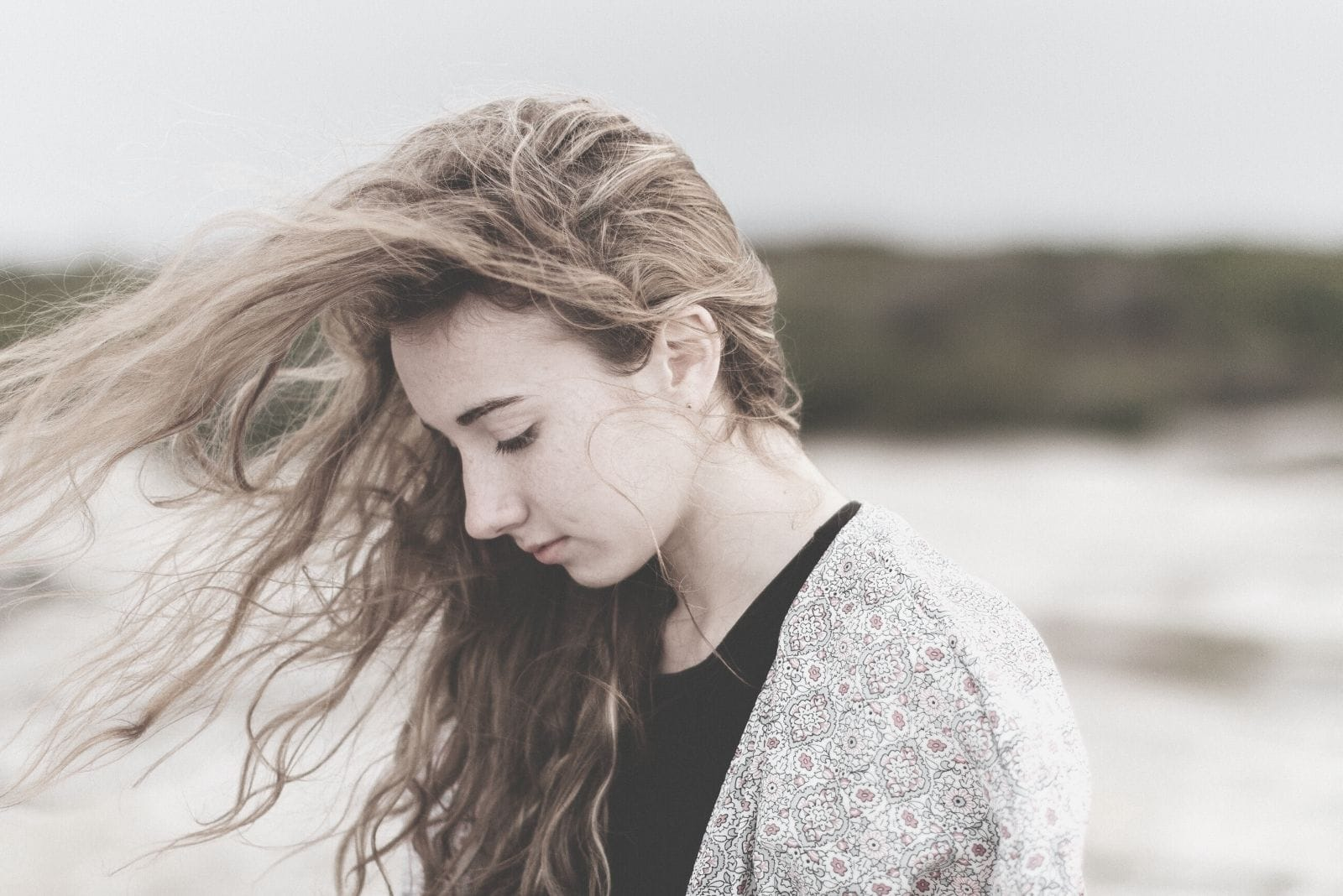 sad young woman near the beach walking with hair blown by the air bowing head