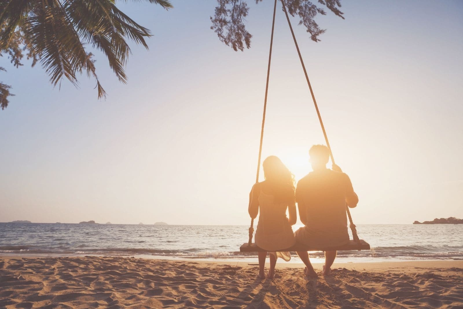 silhouette of a couple in love on a honeymoon sitting on the swing in the beach
