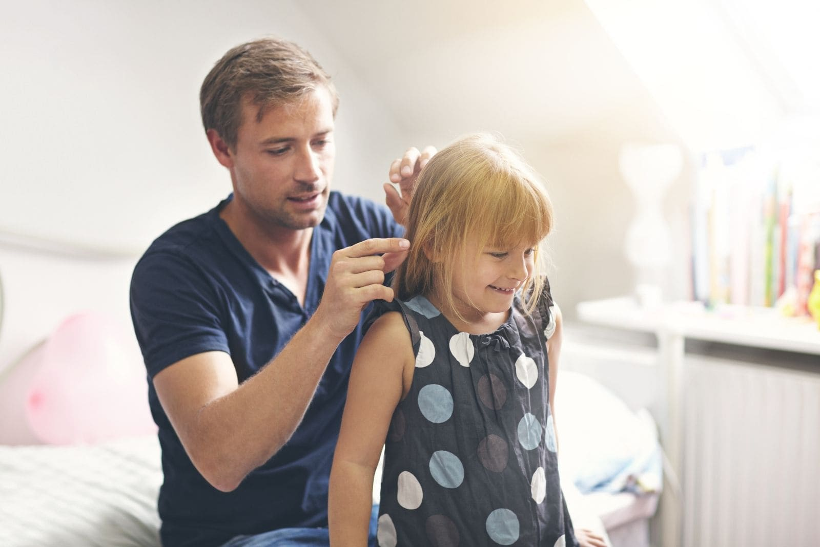 single dad keeping his daughter's hair while sitting inside the room