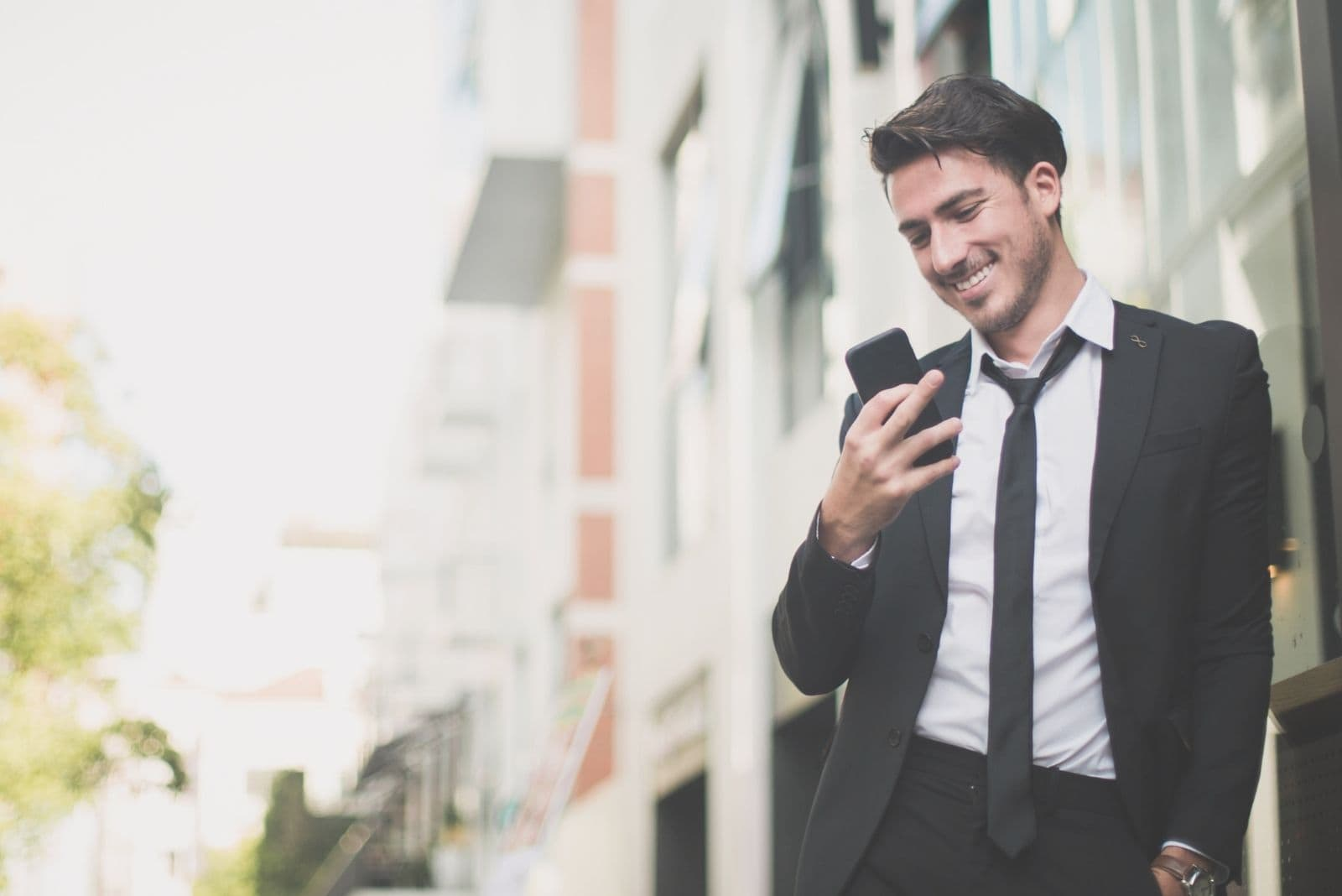 smiling business man texting with his phone leaning on the wall outdoors