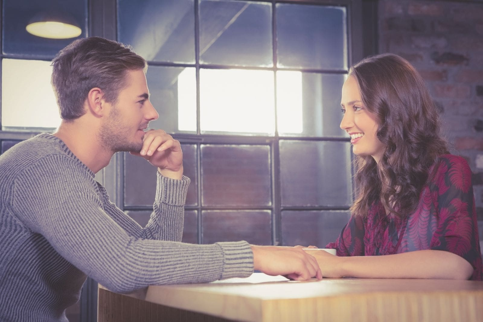 smiling couple talking in a cafe with hands nearly touching
