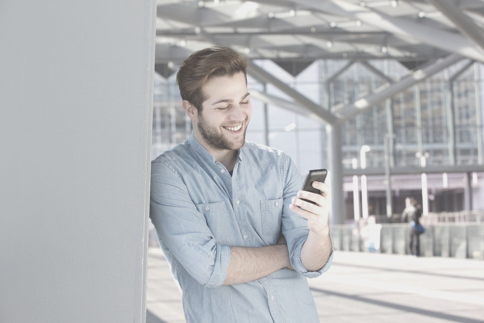 smiling man reading text messages from his phone outside a store