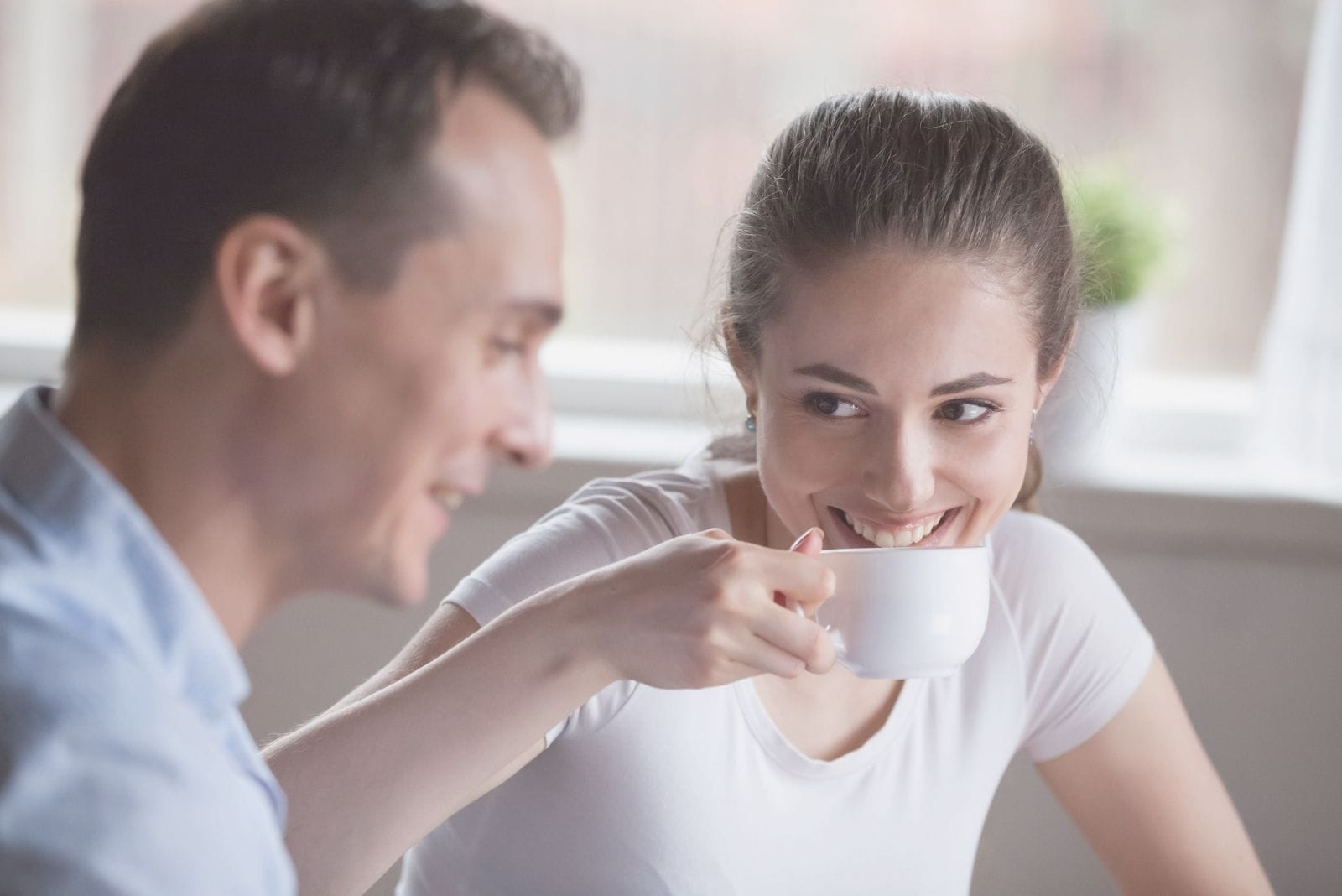 smiling woman drinking coffee with a handsome man indoors