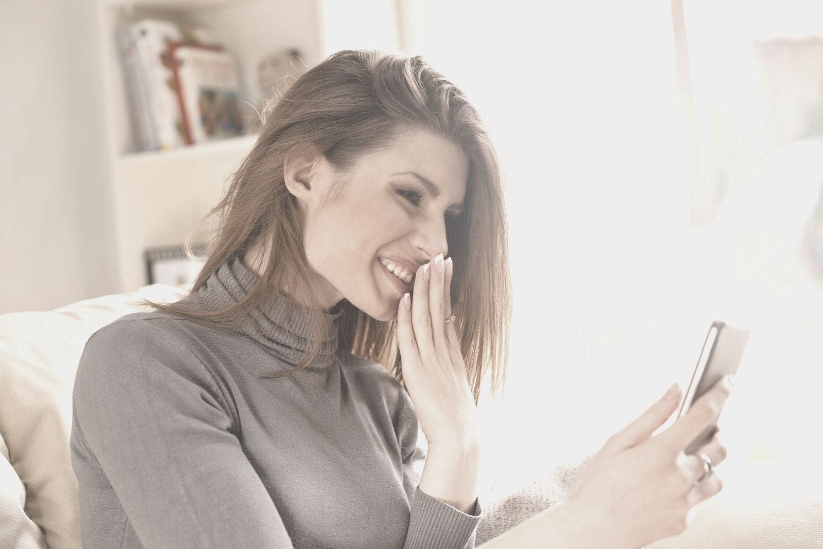 smiling woman giggling over a message in the cellphone wearing turtleneck sitting inside living room