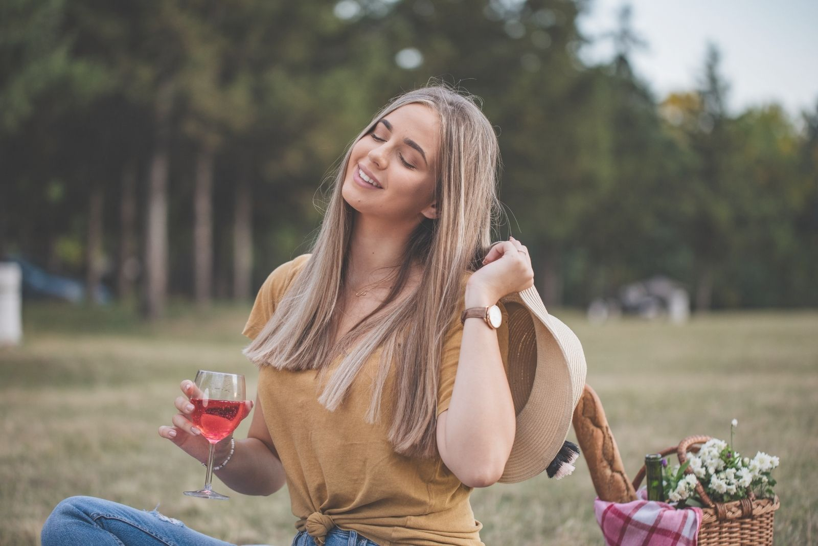 smiling woman in picnic at the park having a good time holding wine