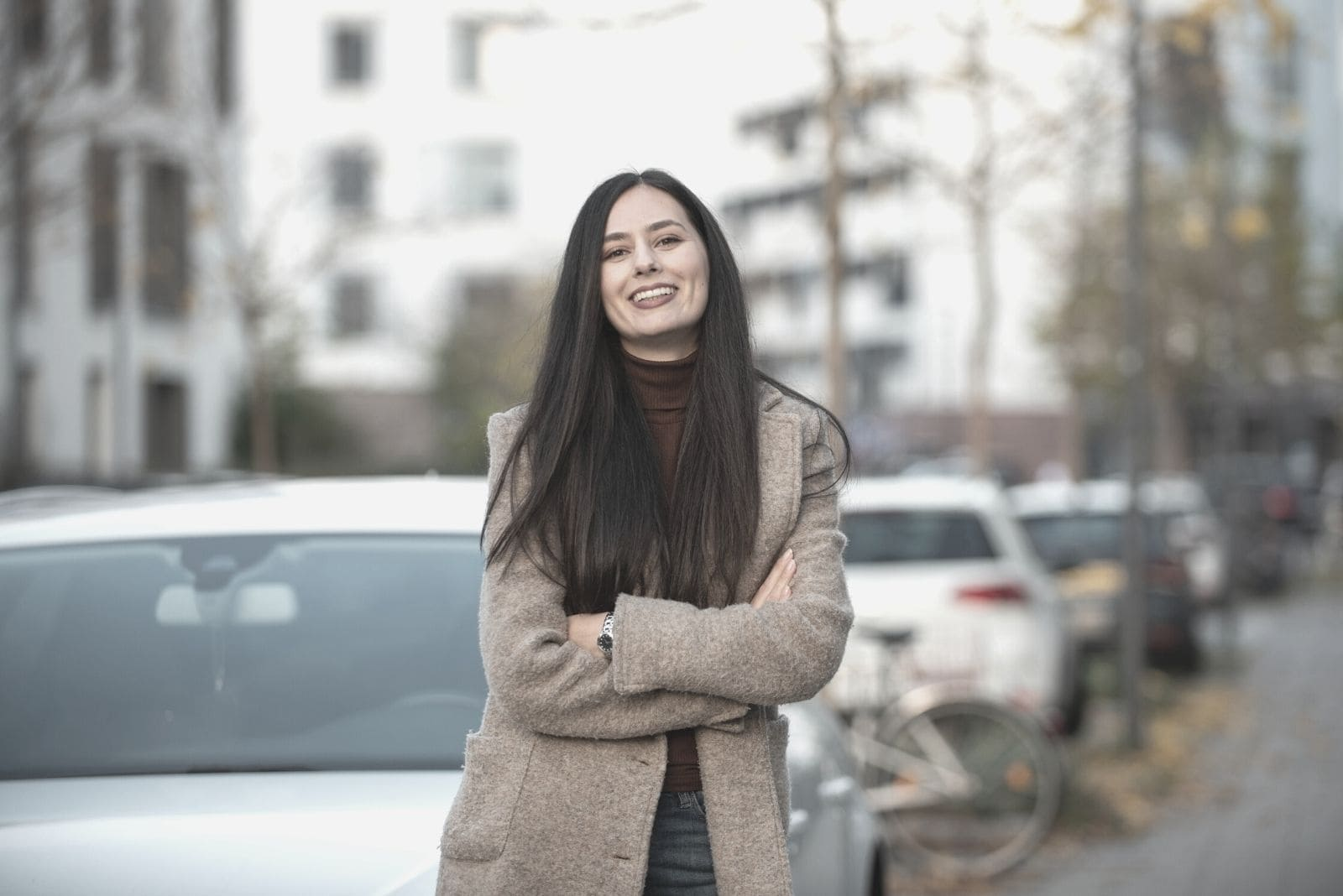 smiling woman outdoor standing in front of the car parked on the side of the street