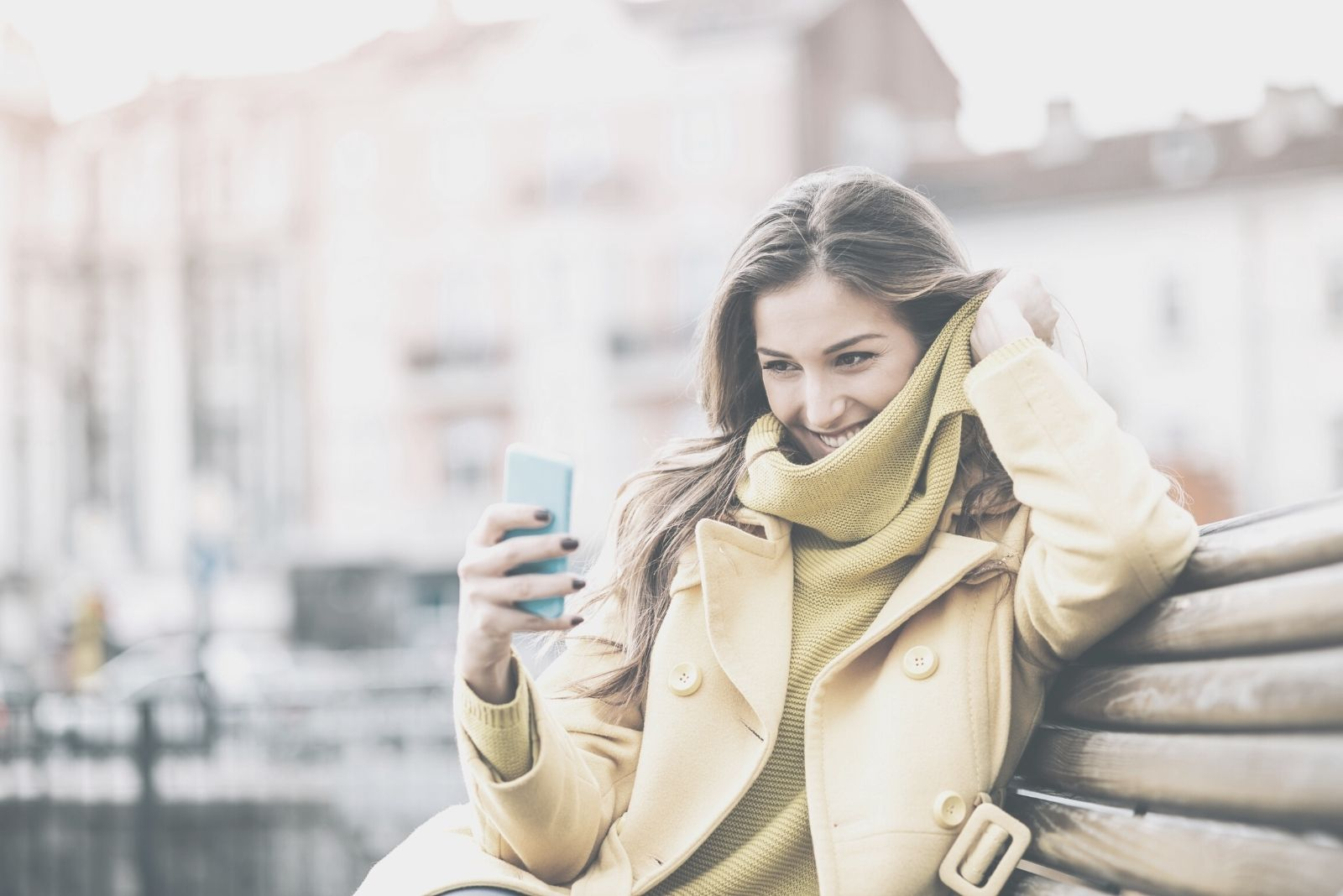 smiling woman texting and sitting in the bench outdoors wearing winter clothes