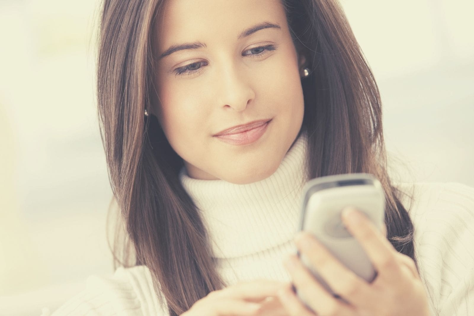 smiling woman using cellphone handheld and texting in close up photography