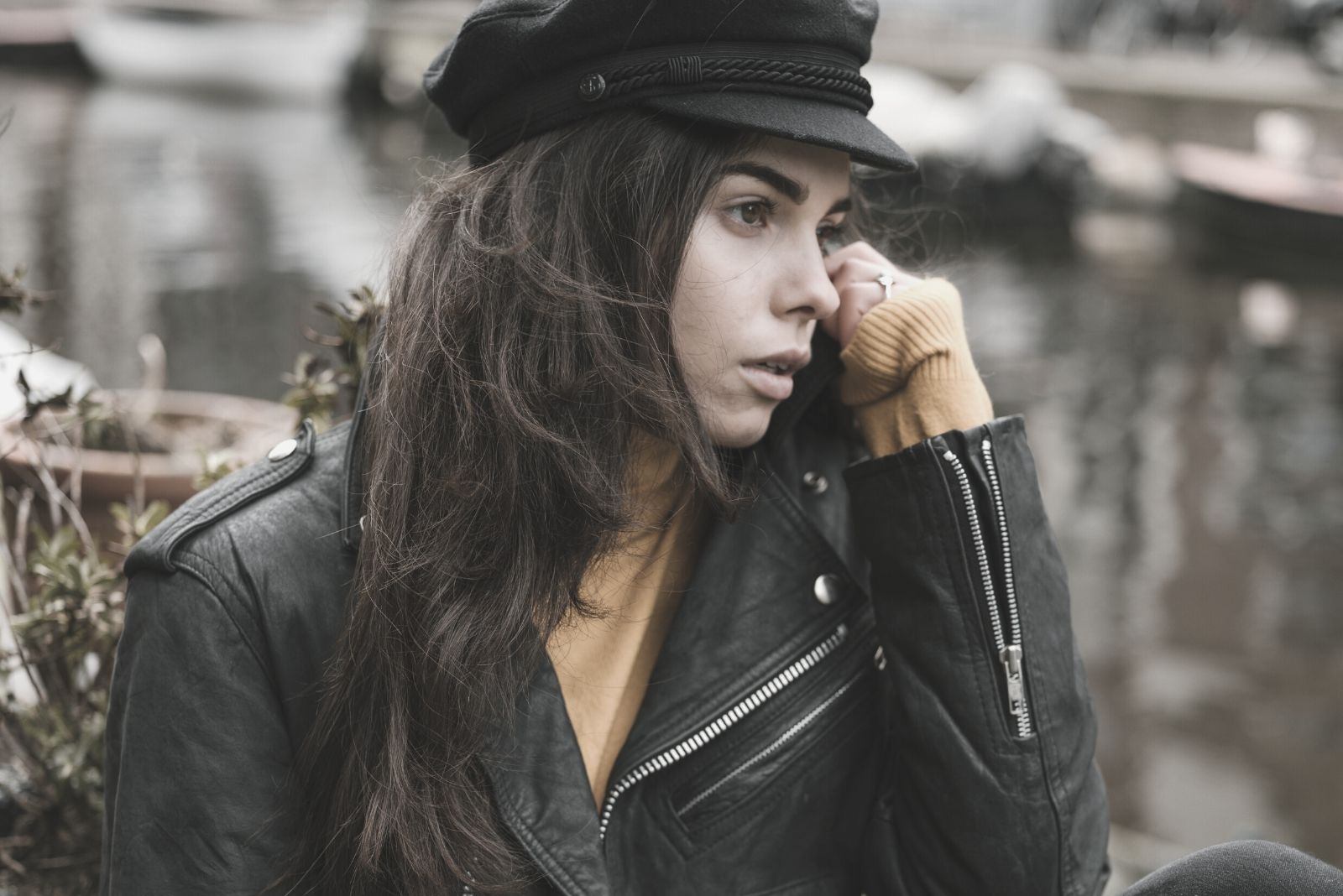 stylish pensive woman resting on a sidewalk near a canal in autumn city