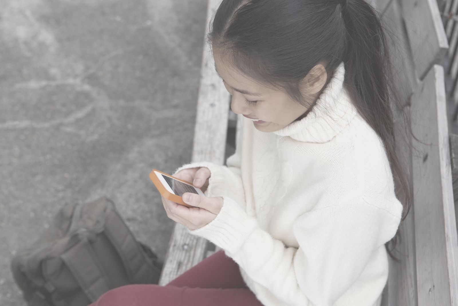top angle of a woman smiling while texting and sitting outdoors