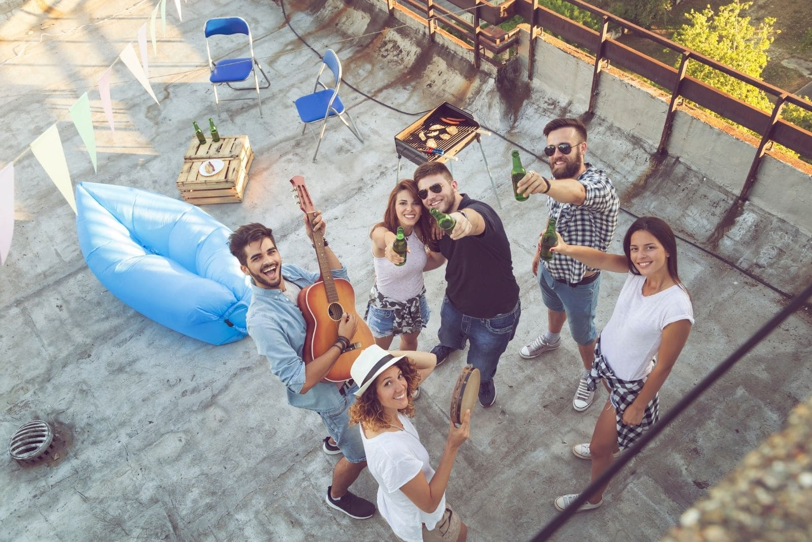 top view of a group of friends hanging out drinking and playing guitar on a roof top party
