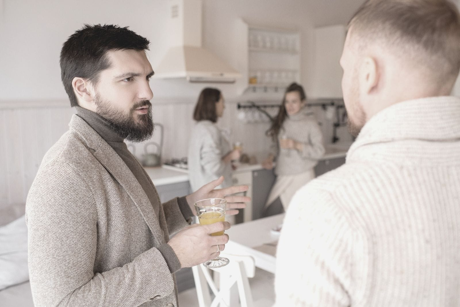two men talking seriously inside the kitchen with two women talking at the background