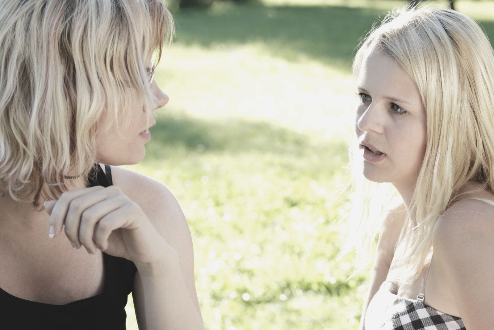 two young caucasian women talking seriously in the park in close up image