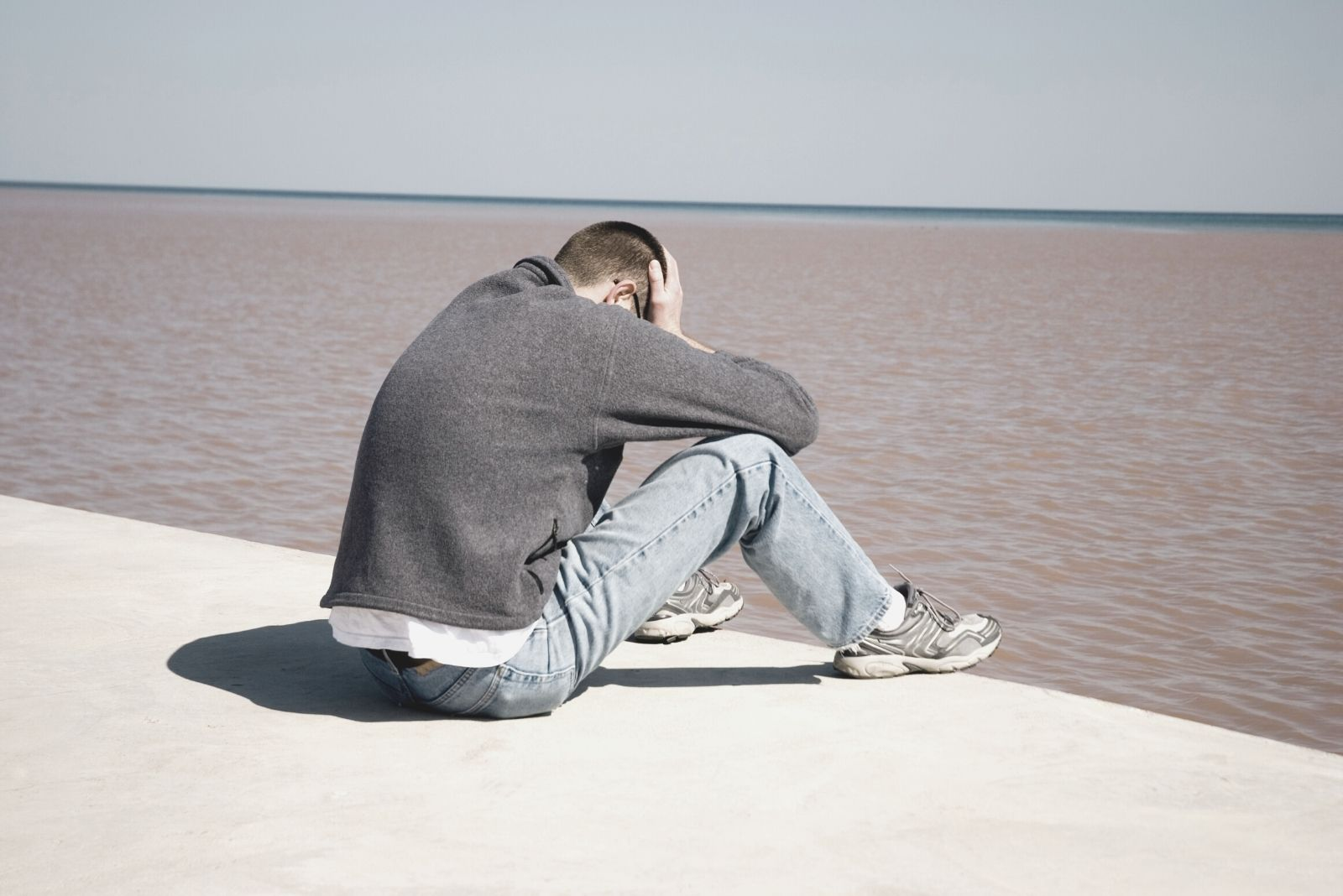 upset man sitting on the platform near the body of water with hand on his head