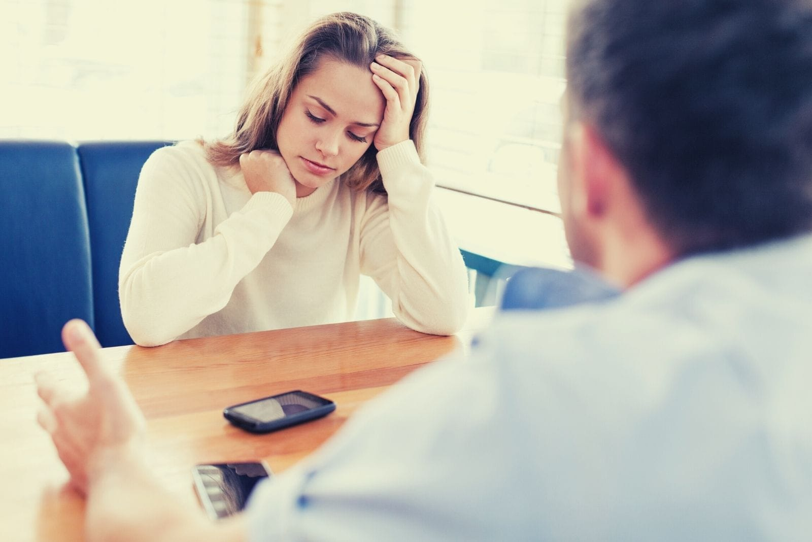 upset woman sitting infront of a guy sitting inside the cafe with a phone on top of the table