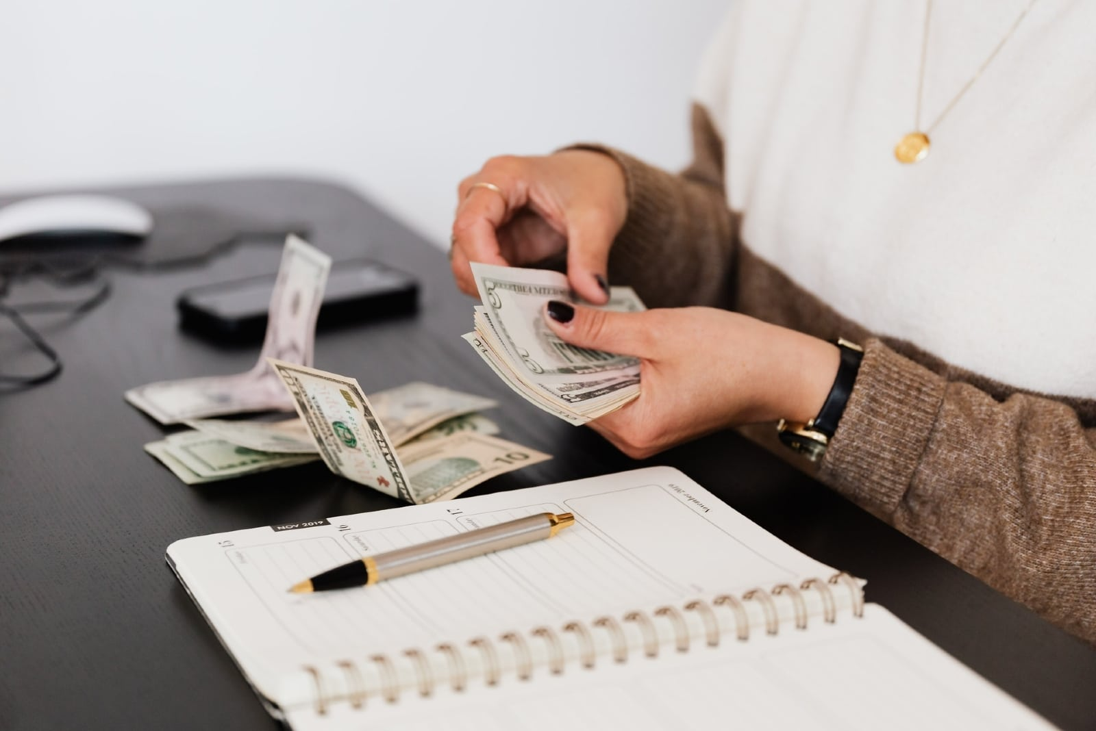 woman counting money while sitting at table